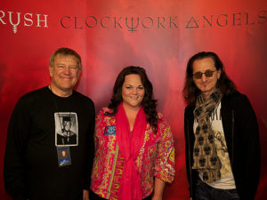 Lisa Kirkwood with Alex Lifeson and Geddy Lee of Rush